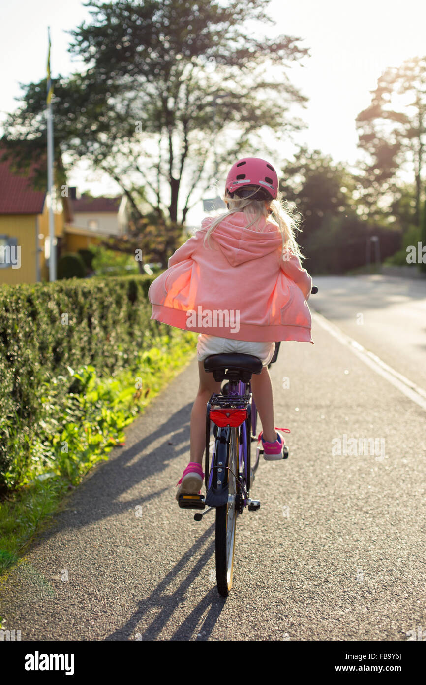 Sweden, Vastergotland, Lerum, Girl (10-11) wearing pink helmet riding bicycle along street - Stock Image