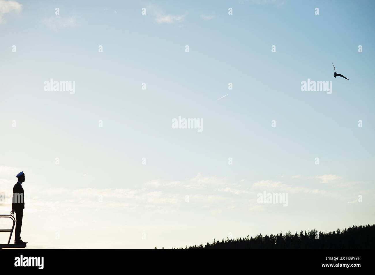 Sweden, Vastmanland, Silhouette of young man wearing mortarboard standing against sky - Stock Image