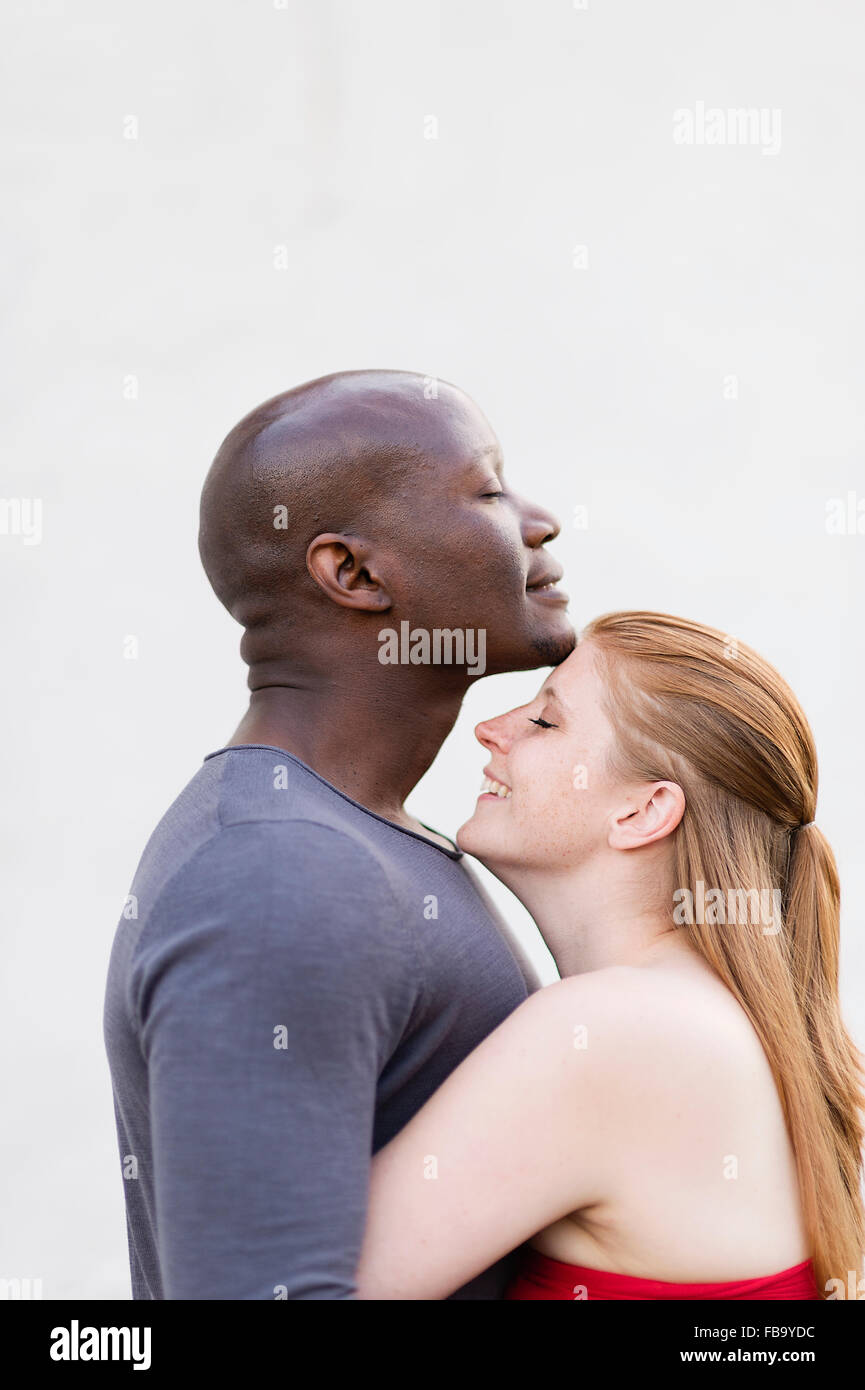 Sweden, Studio shot of mid adult couple embracing - Stock Image