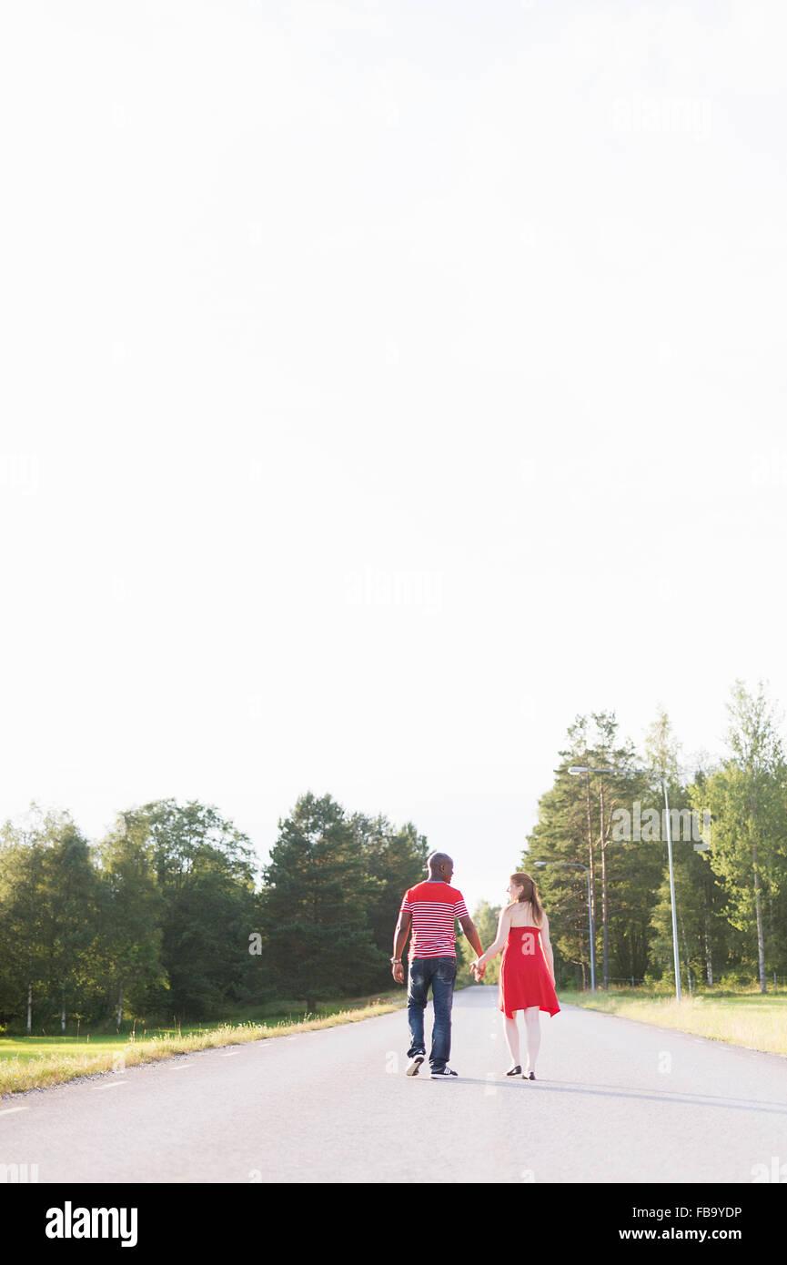 Sweden, Vastmanland, Bergslagen, Hallefors, Rear view of mid adult couple walking on rural road - Stock Image