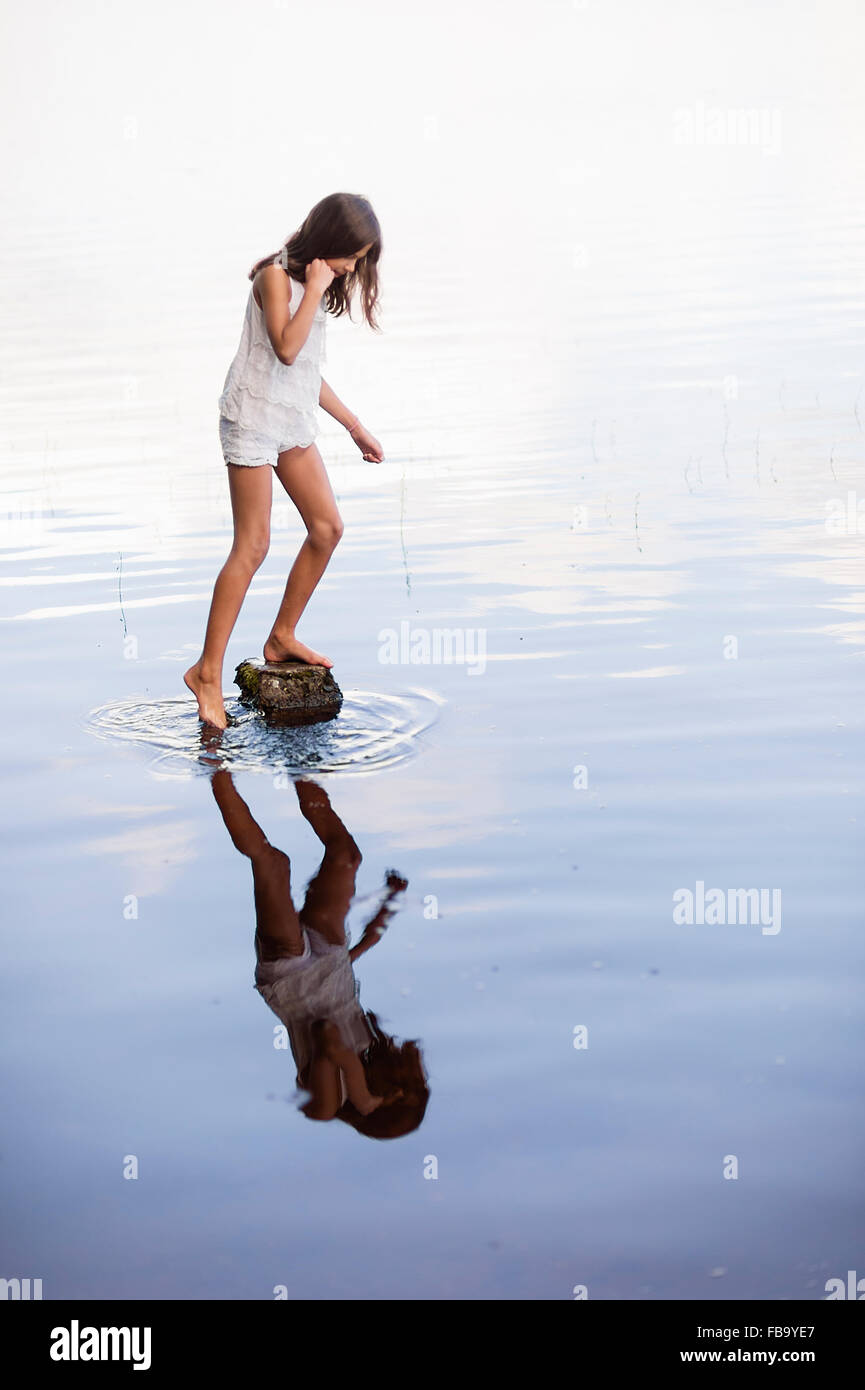 Sweden, Vastmanland, Bergslagen, Svartalven, Girl (8-9) standing on rock in river - Stock Image
