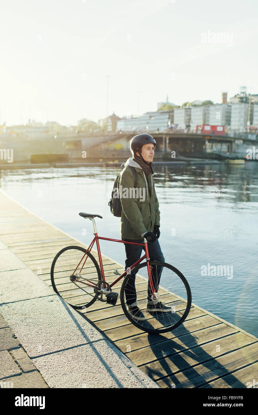 Sweden, Sodermanland, Stockholm, Sodermalm, Slussen, Mid adult man standing with fixed gear bike on jetty - Stock Image