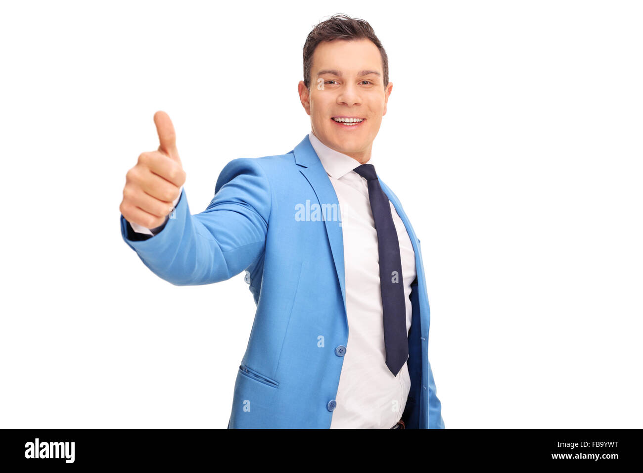 Young cheerful man in a blue suit giving a thumb up isolated on white background - Stock Image