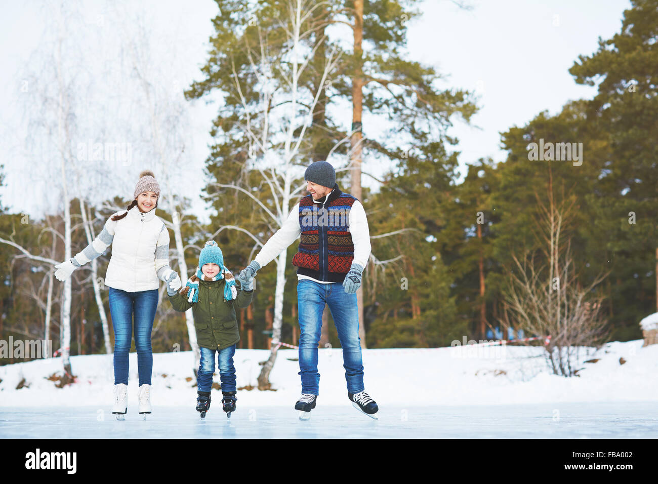 Family ice skating in the park - Stock Image