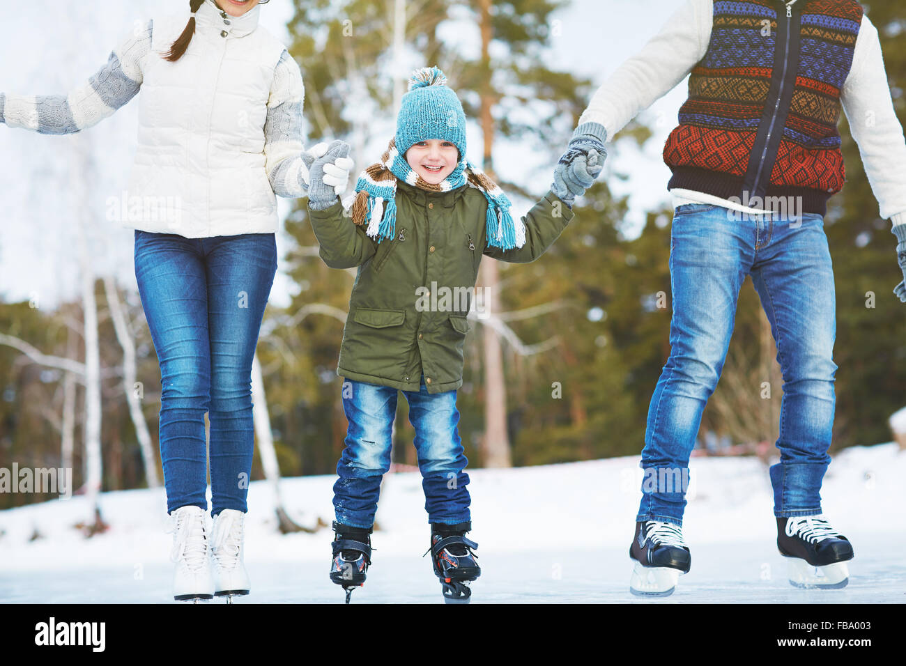 Happy little boy ice-skating with his parents together - Stock Image