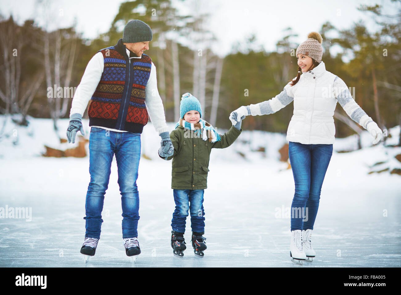 Young family holding hands and ice skating on rink - Stock Image