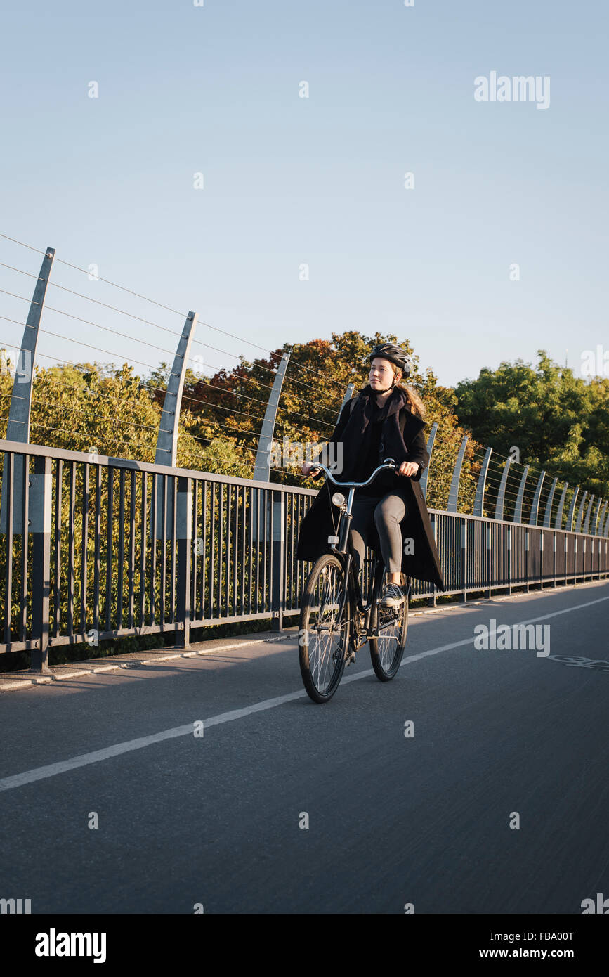 Sweden, Sodermanland, Stockholm, Vasterbron, Young woman riding bike - Stock Image