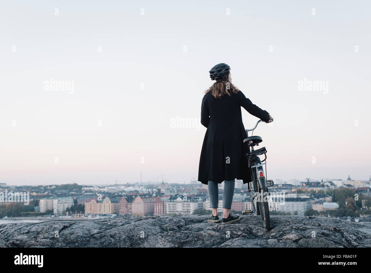 Sweden, Sodermanland, Stockholm, Sodermalm, Skinnarviksberget, Rear view of young woman standing by bicycle on rock - Stock Image