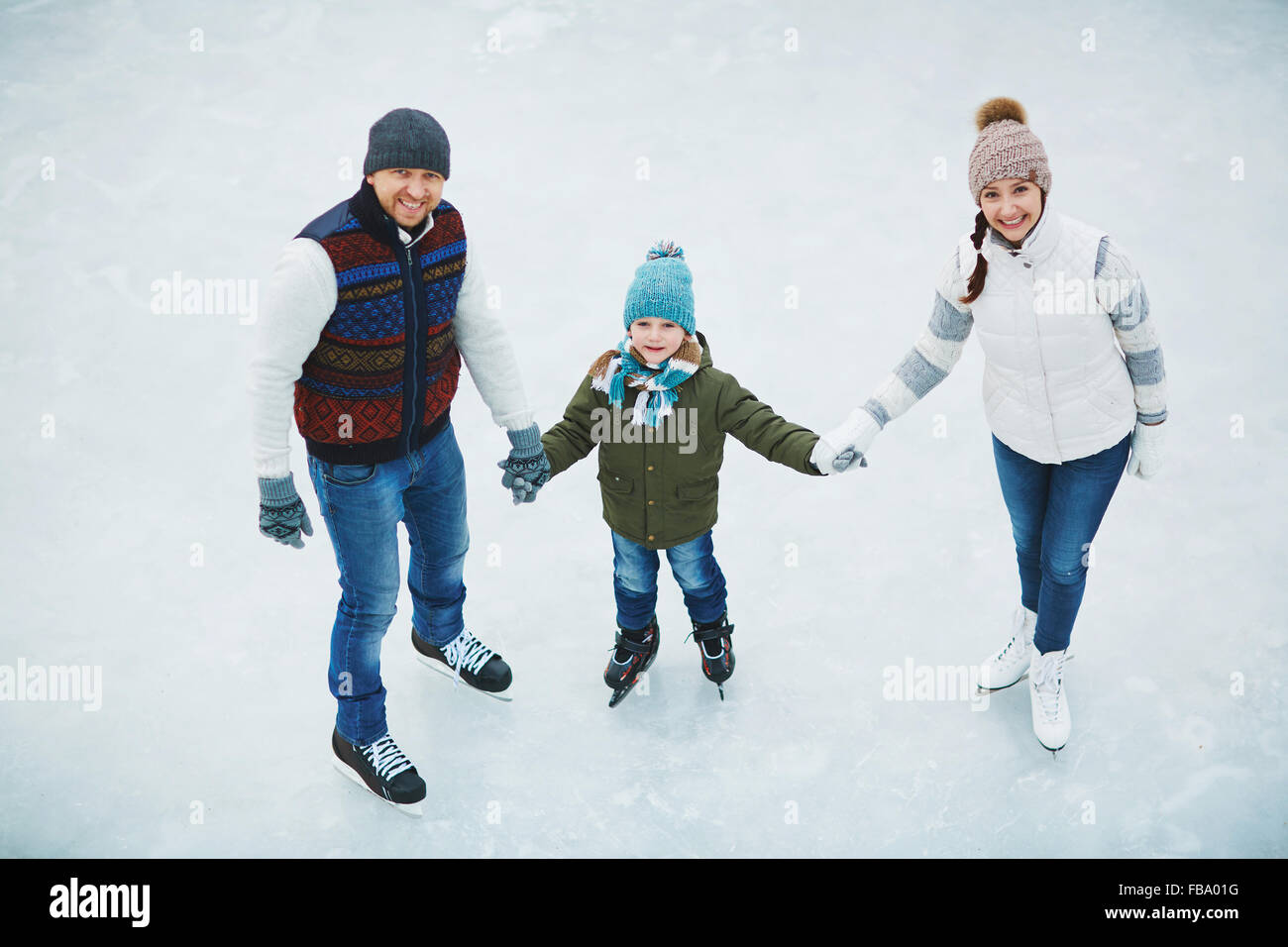 Two parents with son skate in ice skating in winter - Stock Image