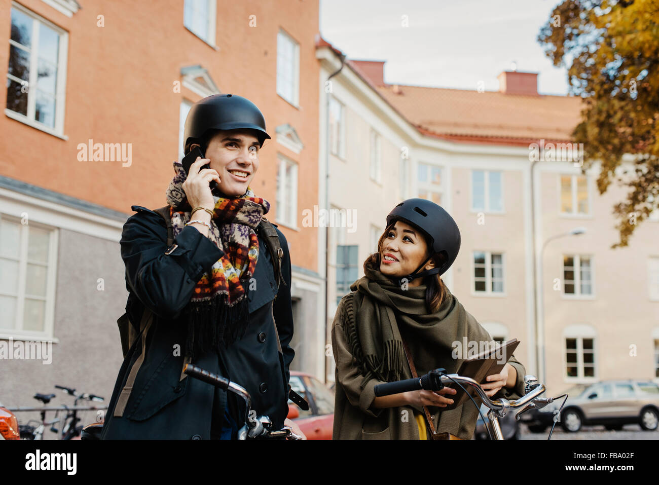 Sweden, Uppland, Stockholm, Vasastan, Rodabergsbrinken, Two people standing with bicycles outdoors - Stock Image