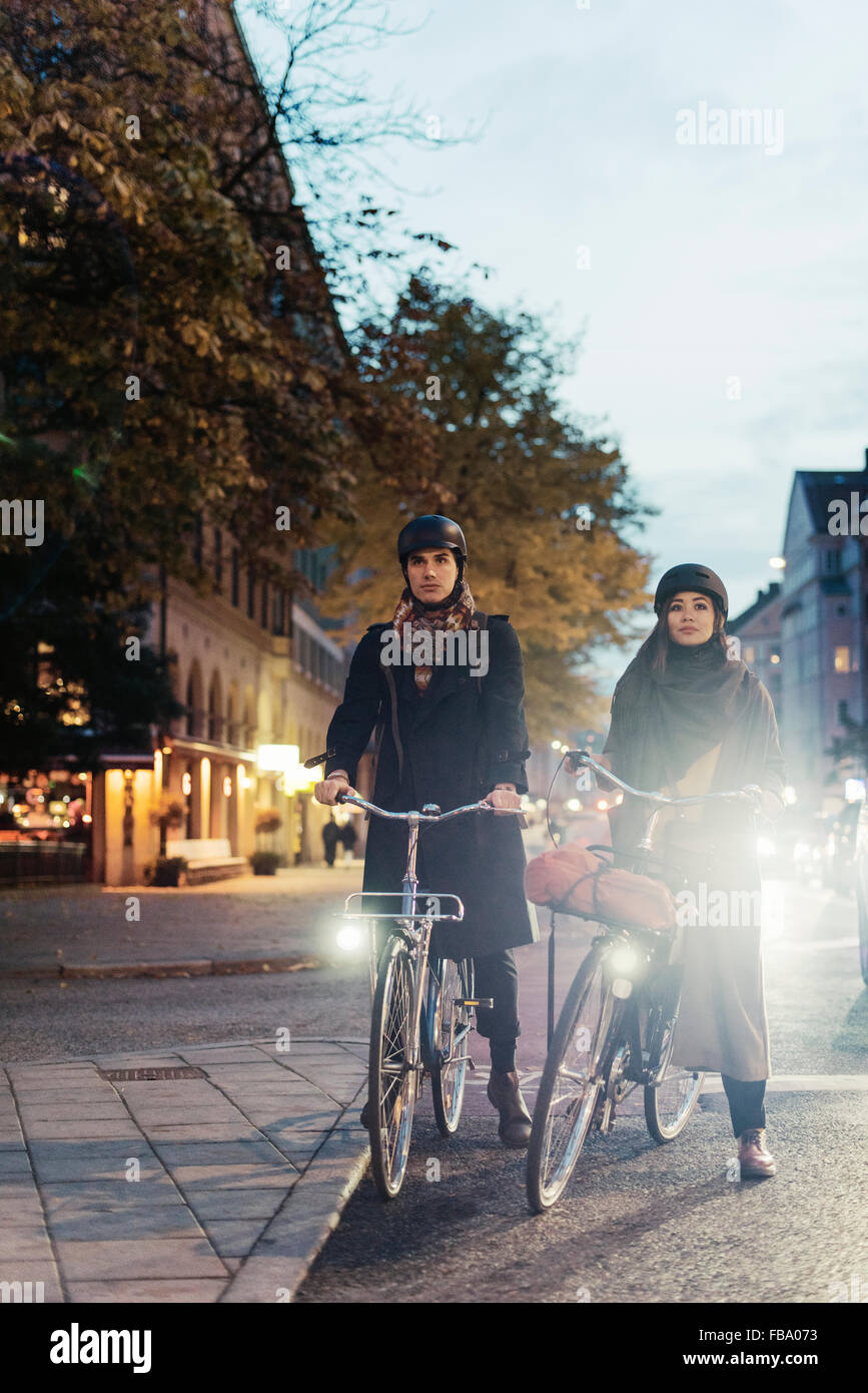 Sweden, Uppland, Stockholm, Vasatan, Sankt Eriksgatan, Man and woman cycling on city street Stock Photo