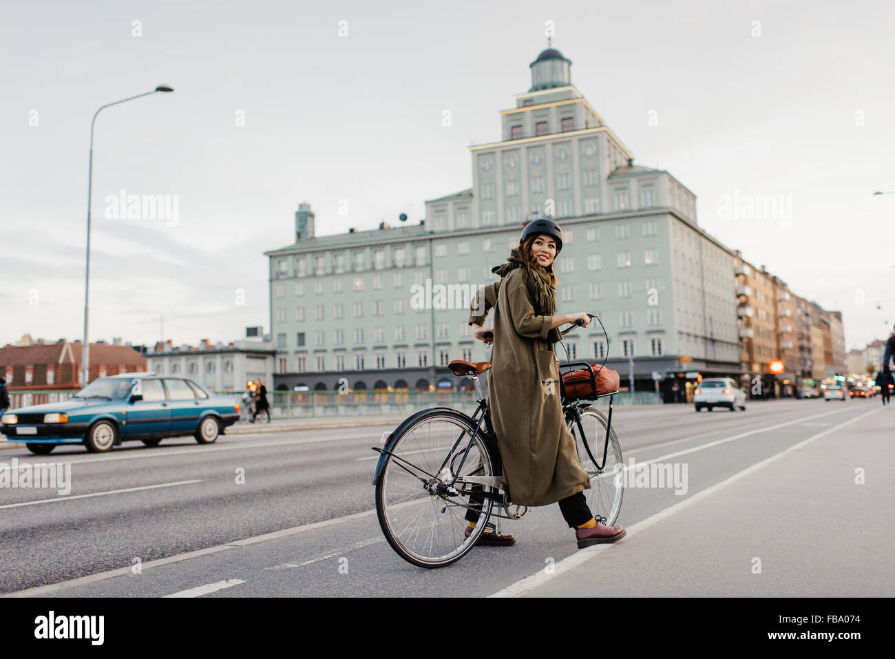 Sweden, Uppland, Stockholm, Vasatan, Sankt Eriksgatan, Woman cycling on city street - Stock Image