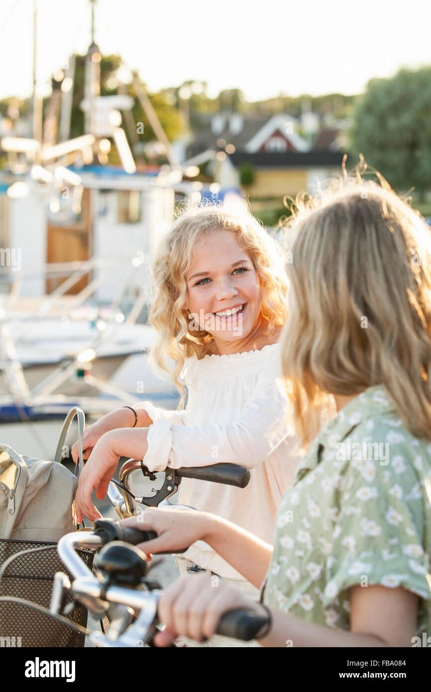Sweden, Blekinge, Hallevik, Two teenage girls(14-15, 16-17) with bicycles at marina bay - Stock Image