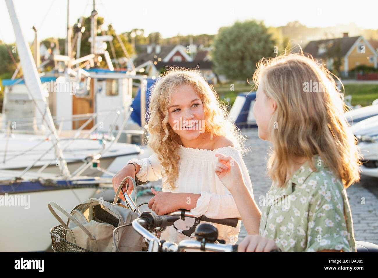 Sweden, Blekinge, Hallevik, Two teenage girls(14-15, 16-17) with bicycles talking at marina bay - Stock Image