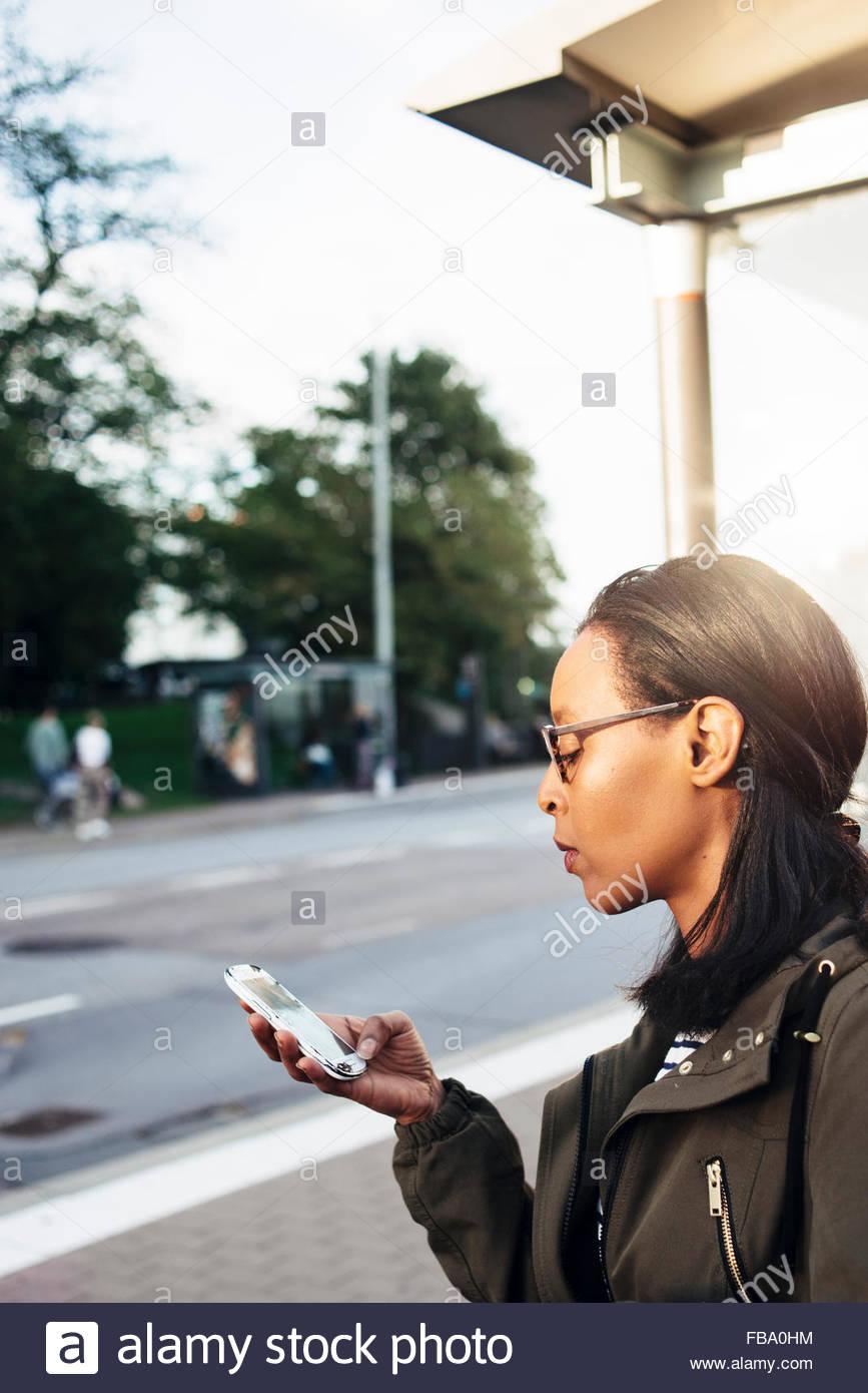 Sweden, Vastra Gotaland, Gothenburg, Woman using smartphone on street - Stock Image