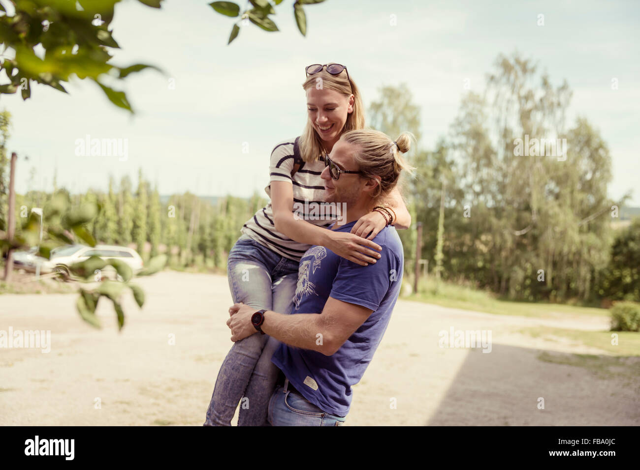 Sweden, Skane, Ostra Goinge, Man carrying girlfriend - Stock Image