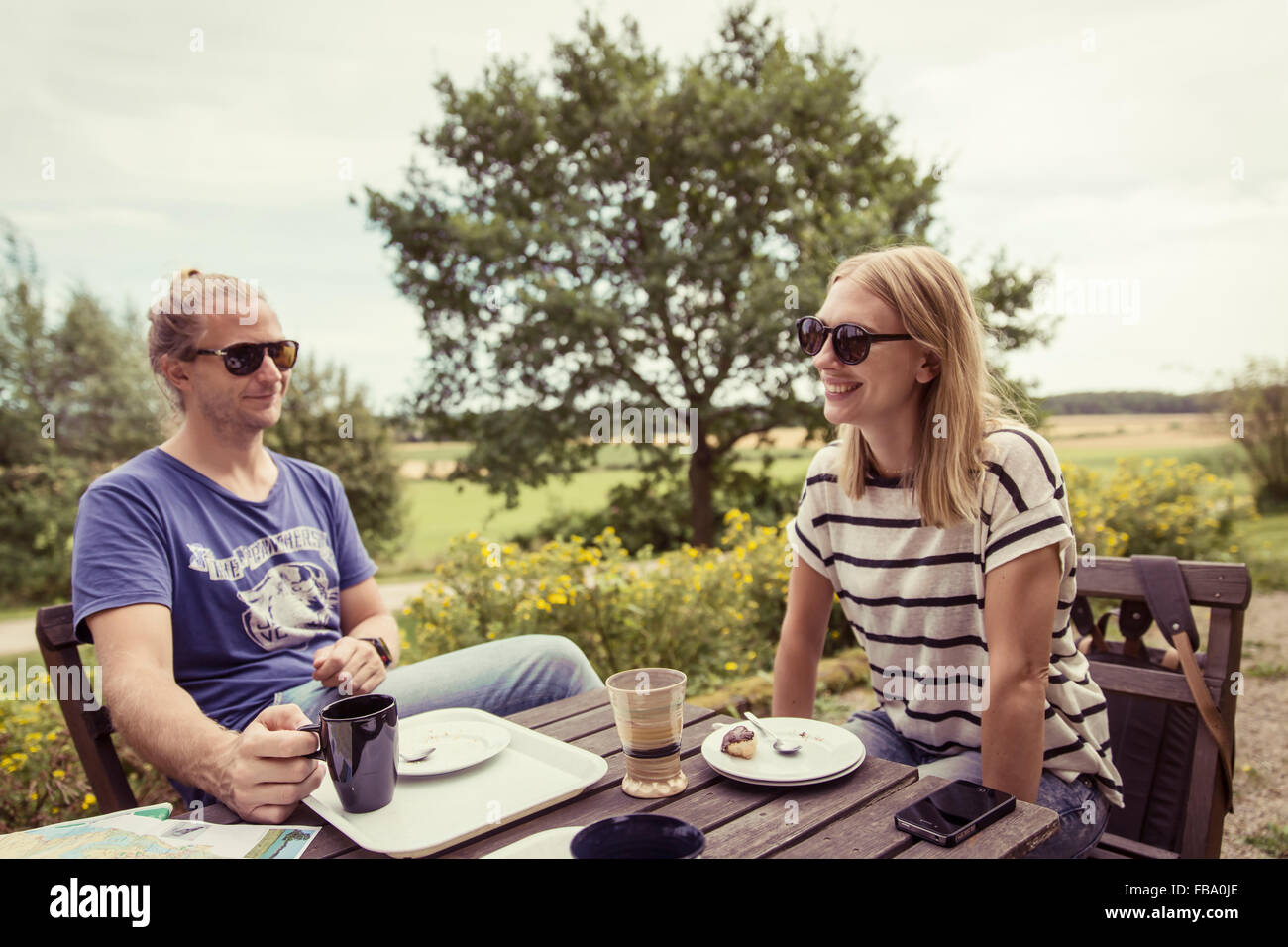 Sweden, Skane, Ostra Goinge, Couple relaxing at table - Stock Image