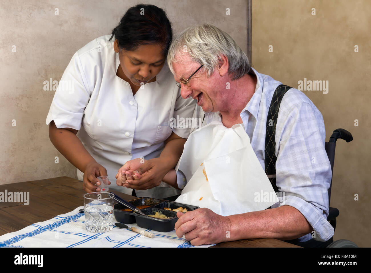 Nurse in old people's home trying to make a patient eat his dinner and pills - Stock Image
