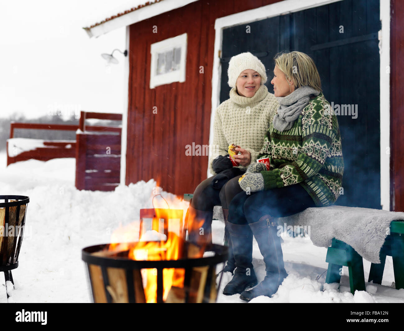 Sweden, Mother talking with teenage girl (14-15) on bench in winter - Stock Image