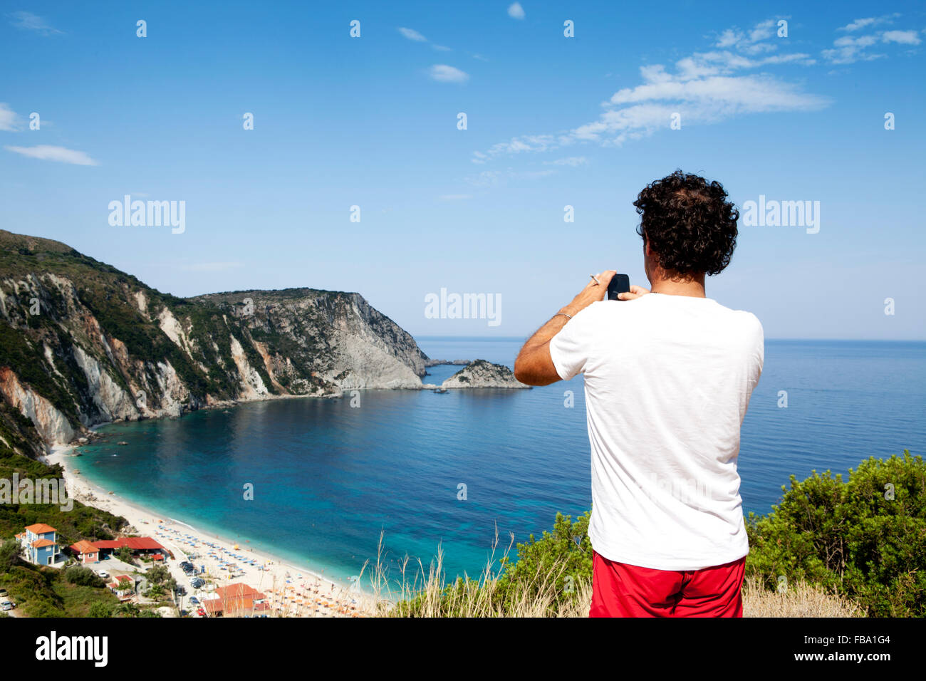 Tourist taking a snapshot of Petani beach bay in Kefalonia, Ionian Islands, Greece - Stock Image