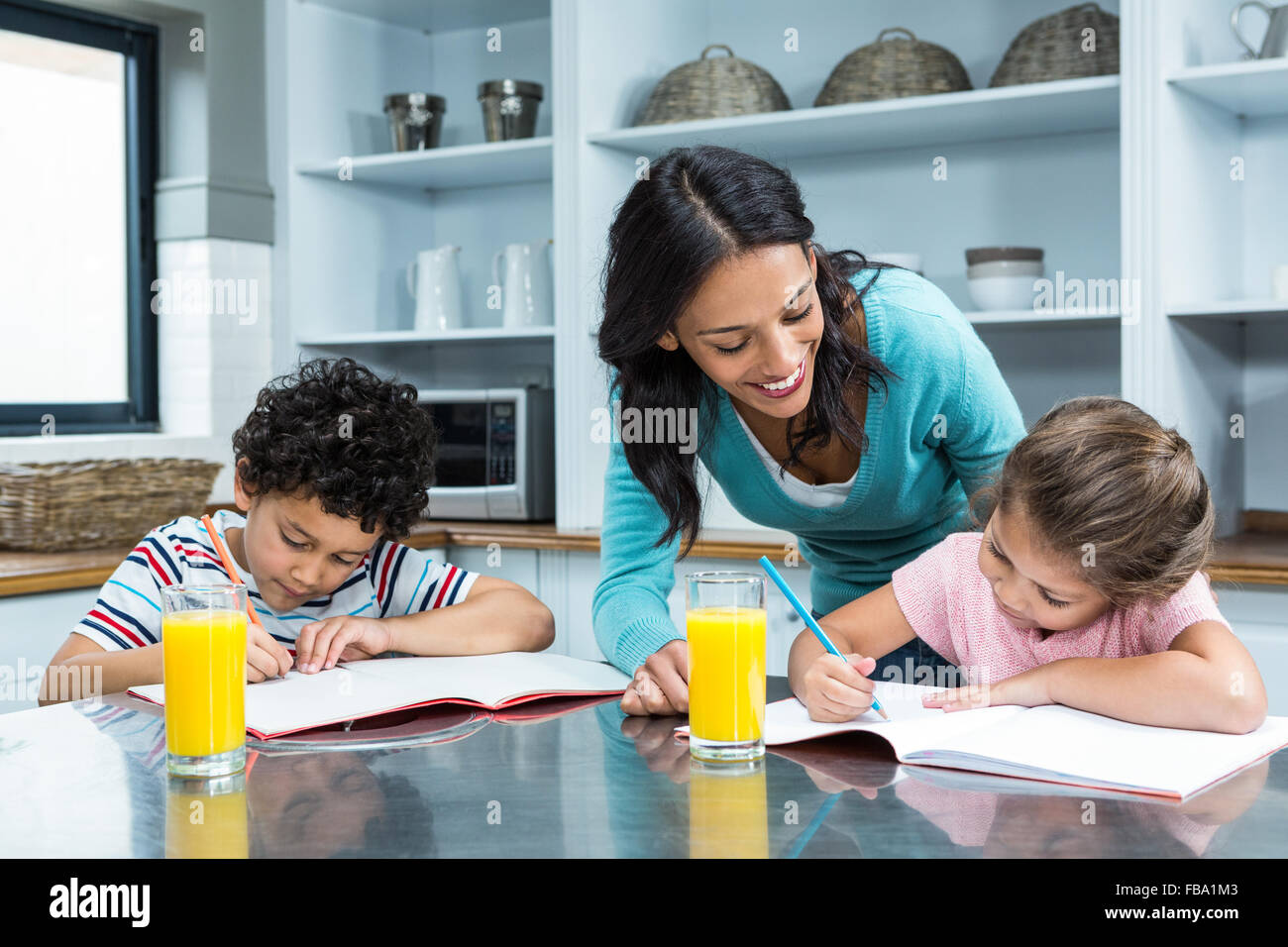 Kind mother helping her children doing homework - Stock Image