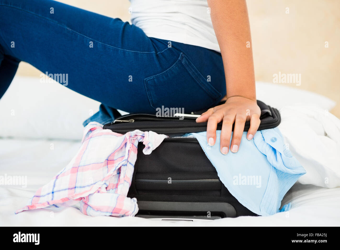 Woman sitting on her overfull suitcase - Stock Image