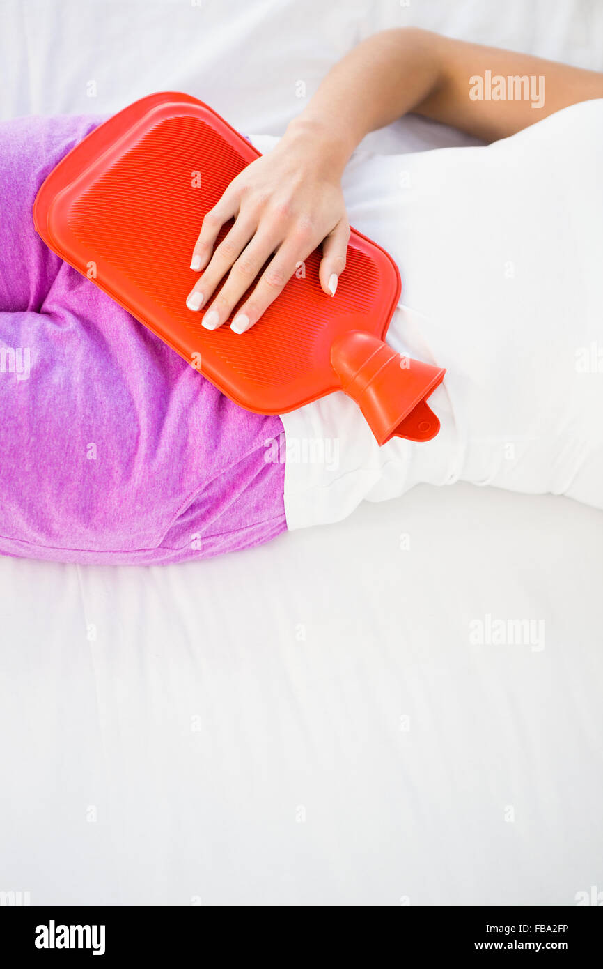 Woman lying on her bed with a belly pain - Stock Image