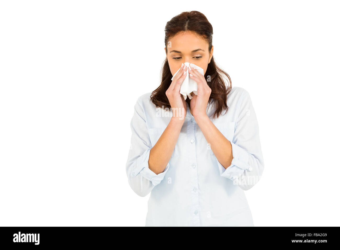Woman blowing nose with tissue paper - Stock Image