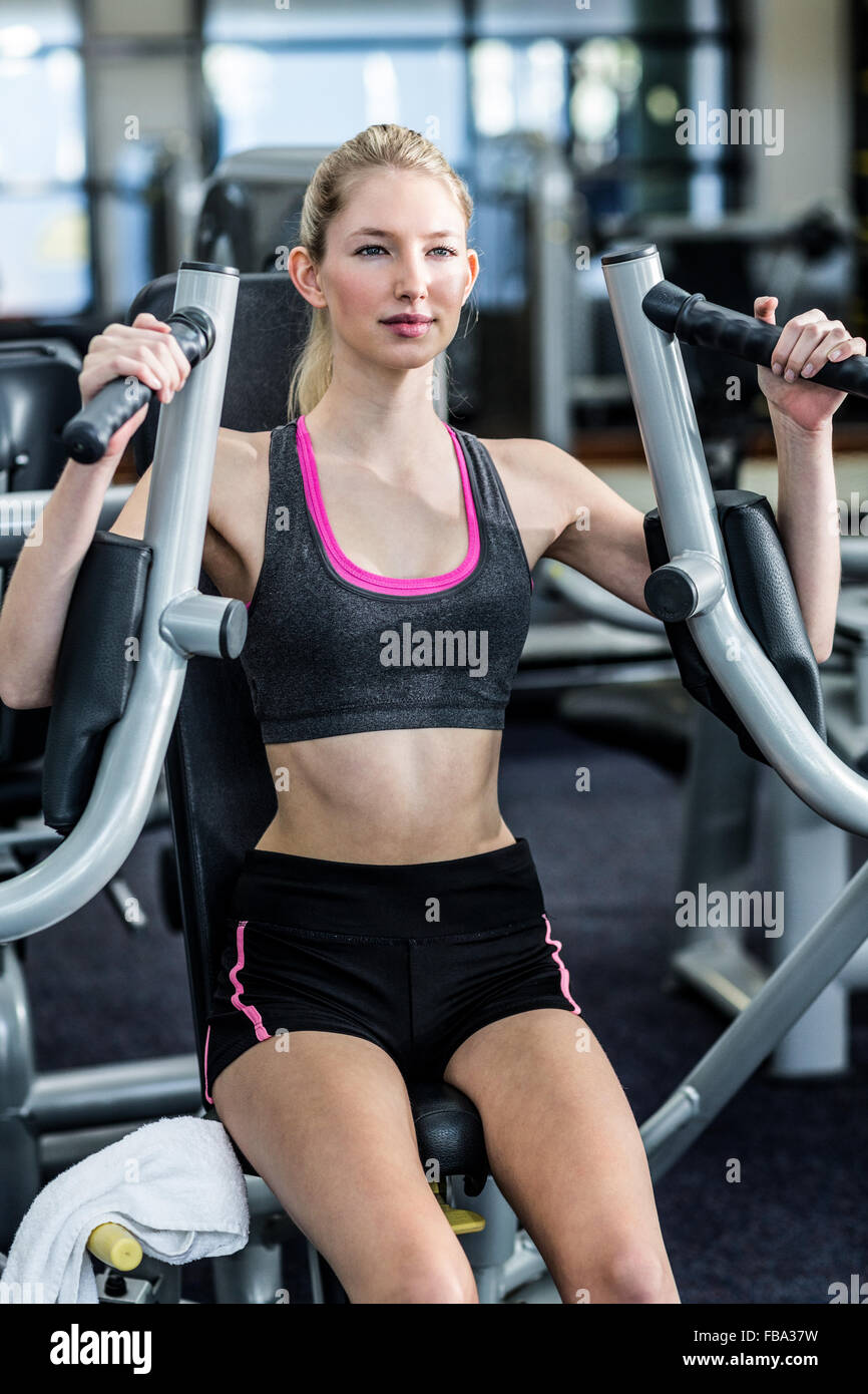 Fit woman using exercise machine - Stock Image