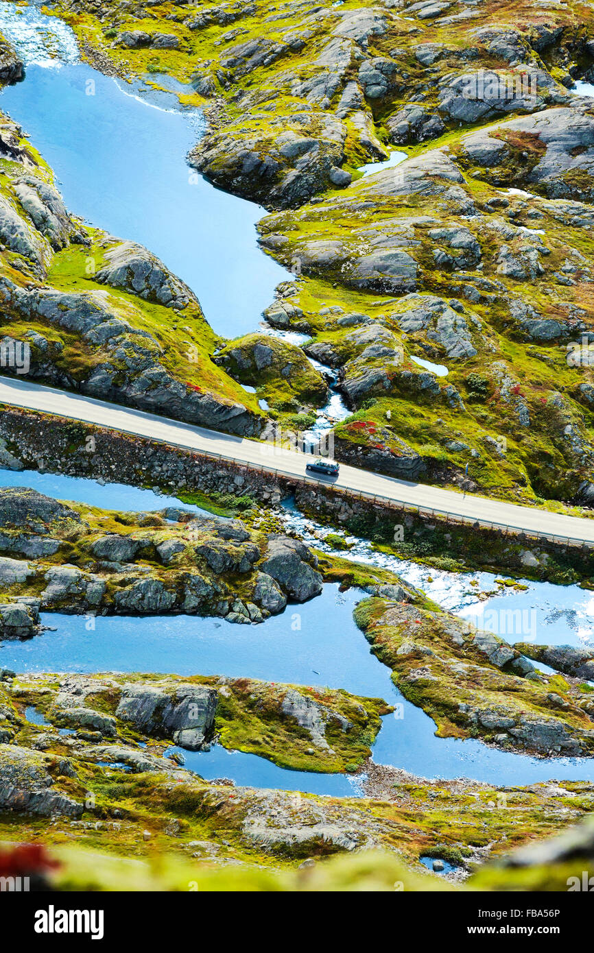 Norway, More og Romsdal, Sunnmore, Elevated view of Geirangerfjord with lone car driving along Trollstigen road - Stock Image