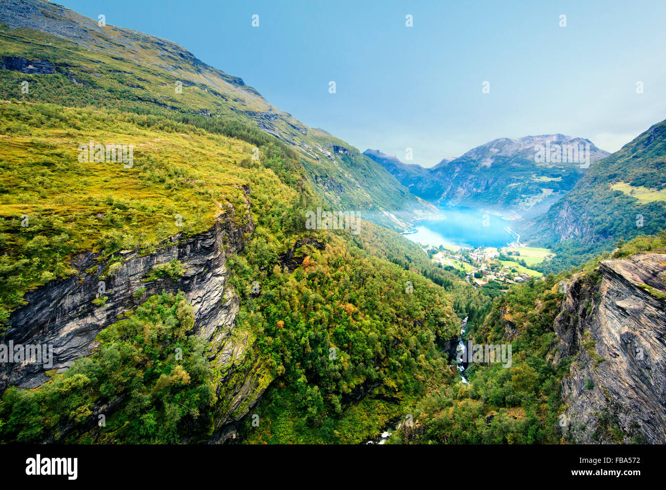 Norway, More og Romsdal, Sunnmore, Geiranger, View along wooded canyon with misty lake - Stock Image