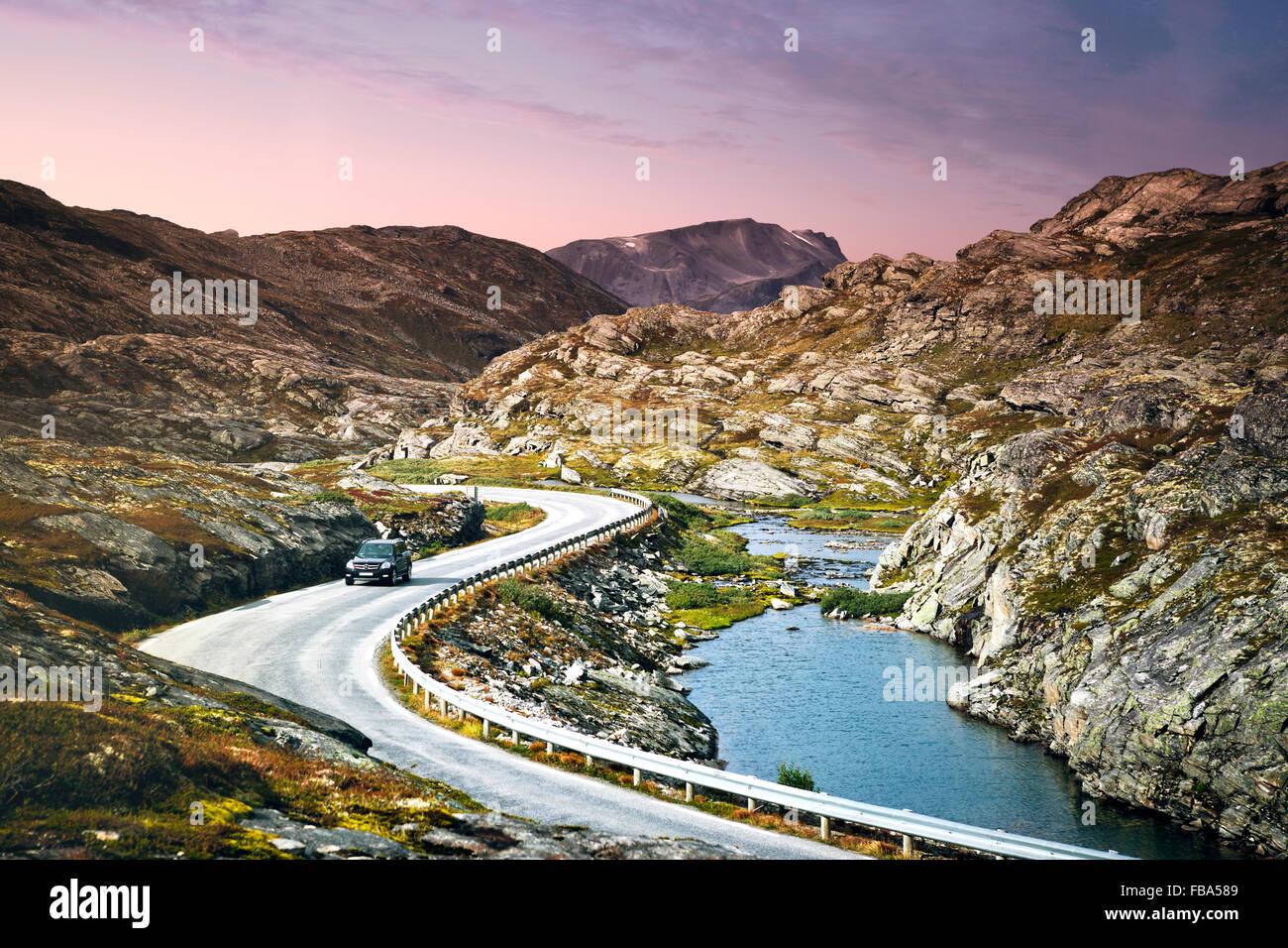Norway, More og Romsdal, Sunnmore, Geirangerfjord, Car driving along Trollstigen Road winding alongside narrow fjord - Stock Image