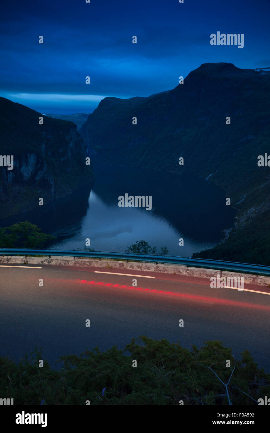 Norway, More og Romsdal, Sunnmore, Geiranger, Still fjord with road and light trail in foreground - Stock Image