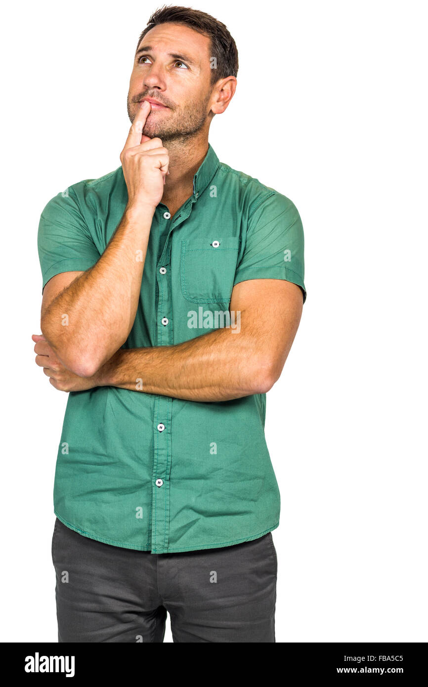 Thoughtful man with finger on lips looking away - Stock Image