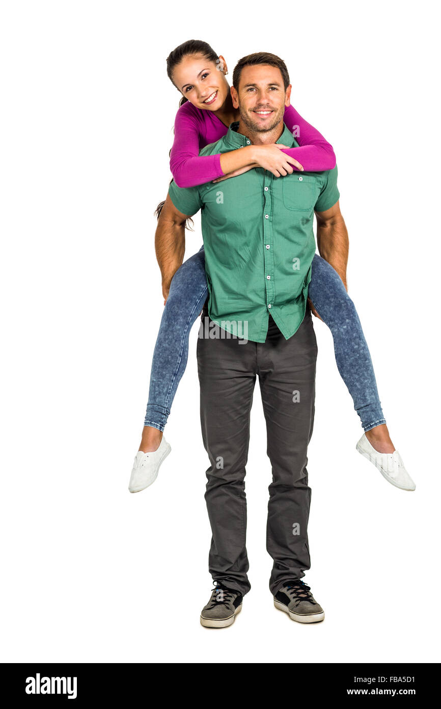 Happy couple giving piggy back - Stock Image