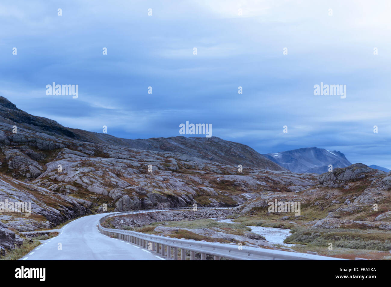 Norway, More og Romsdal, Sunnmore, View of road in mountainous landscape - Stock Image