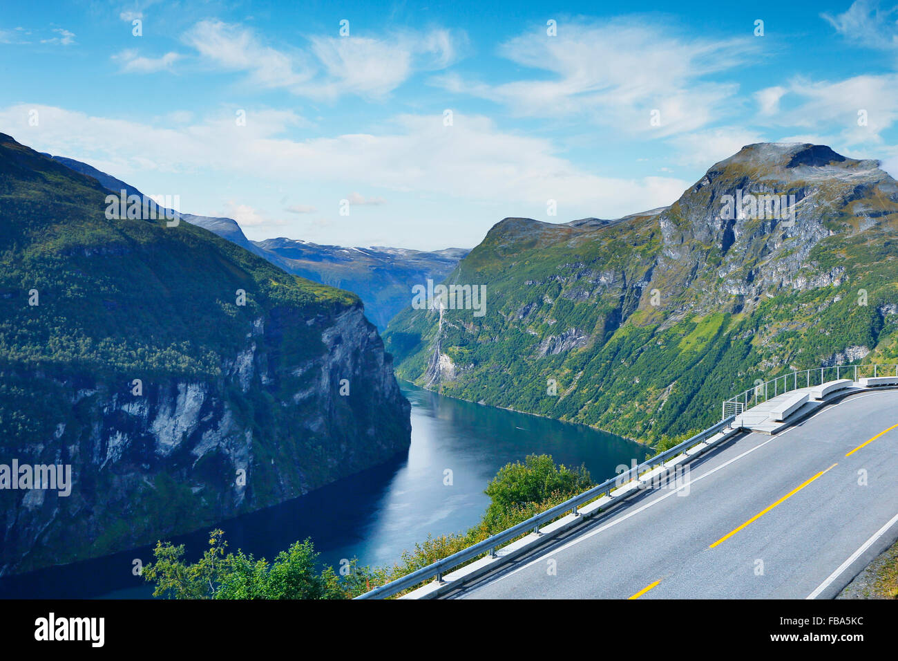 Norway, More og Romsdal, Sunnmore, View of road and lake in mountainous landscape - Stock Image