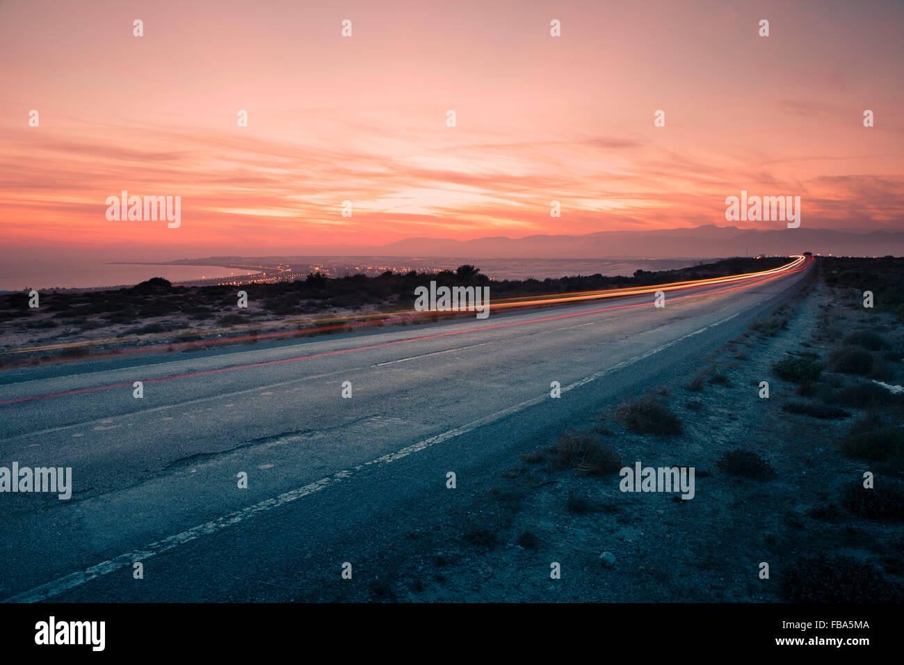 Spain, Almería, Almerimar, View of light trail on road by sea at sunset - Stock Image