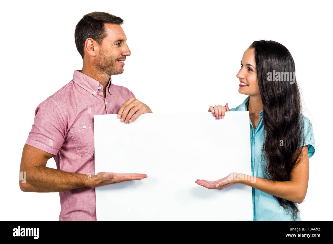 Young couple showing blank sheet - Stock Image