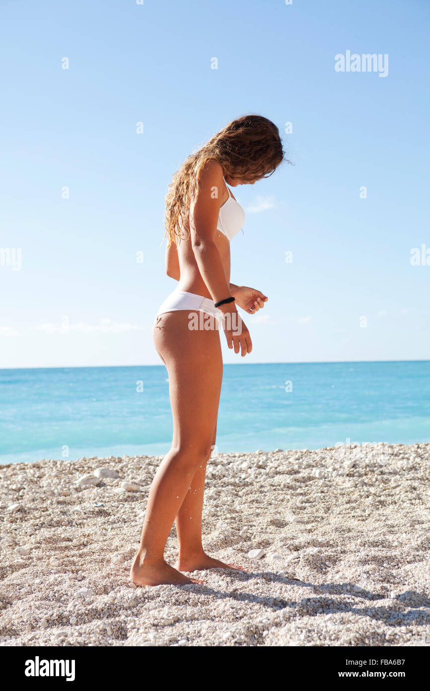 young girl walking on a white sandy beach looking downwards - Stock Image