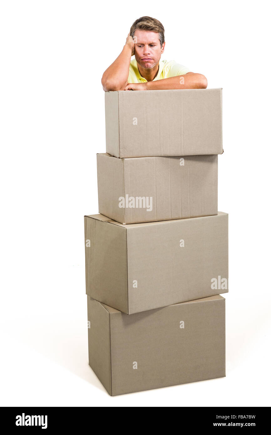 Man thinking while standing with boxes - Stock Image