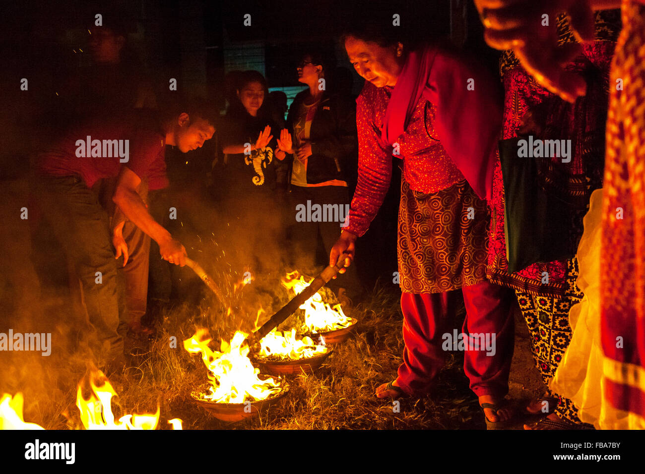Worshipers stoke small fires during the Kumāri Jātrā festival in Kathmandu - Stock Image