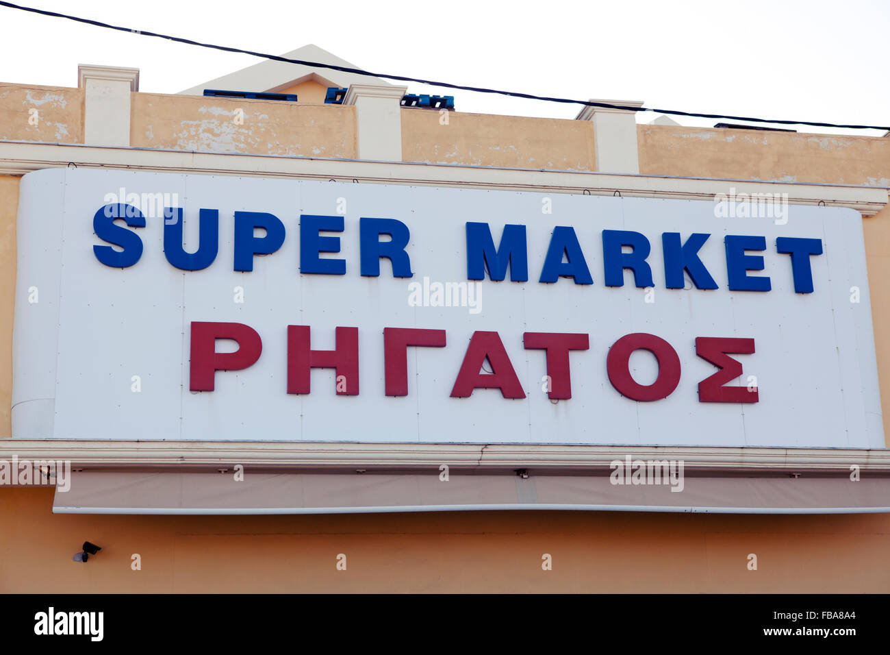 Super market sign, Greek language underneath - Stock Image