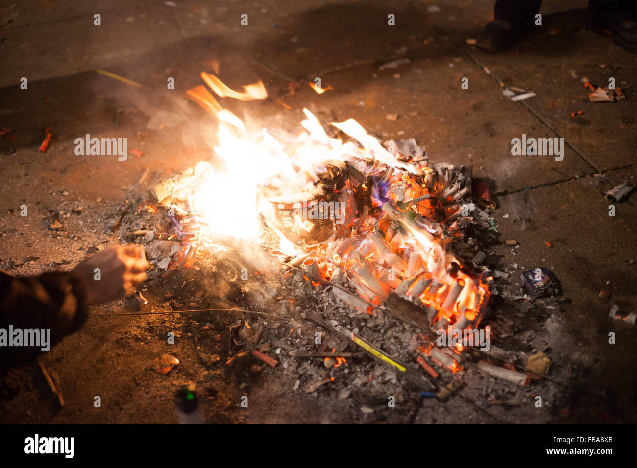Homeless man feeds a fire. Fire built out of spent fireworks by homeless to keep warm, Berlin New Years Eve 2013 Stock Photo