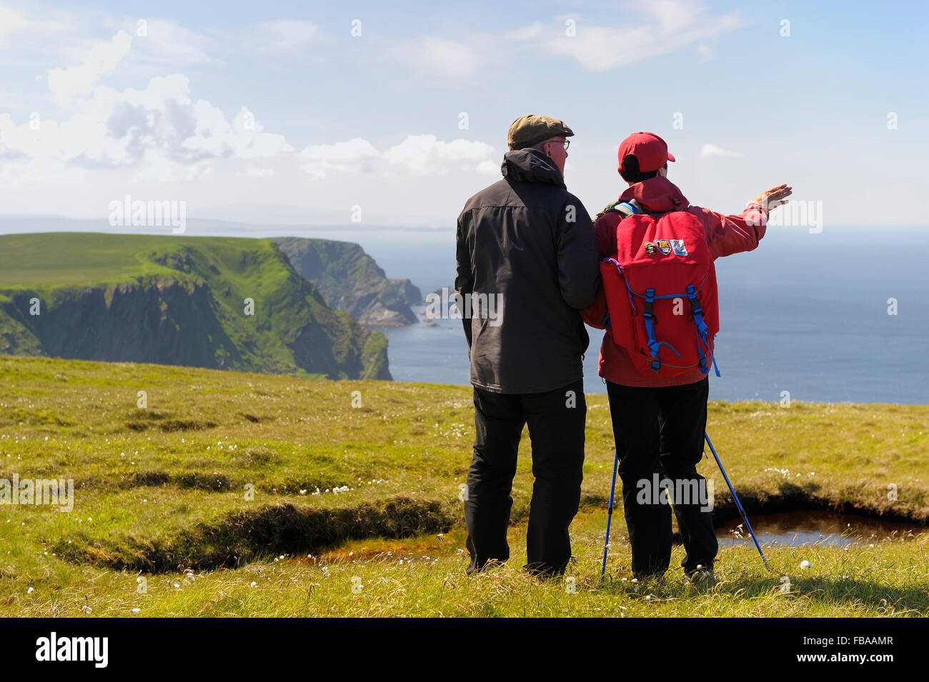 United Kingdom, Scotland, Shetland Islands, Unst, Hermaness, Senior couple looking at sea from grassy cliff - Stock Image