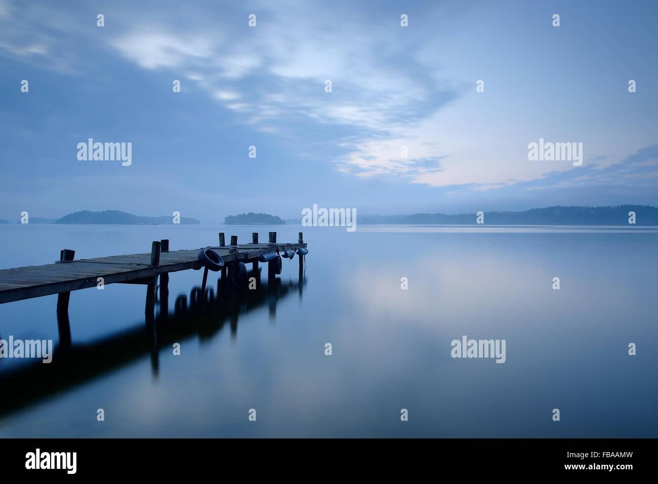 Sweden, Uppland, Stockholm Archipelago, Lidingo, Hoggarnsfjarden, Pier extending into calm bay - Stock Image