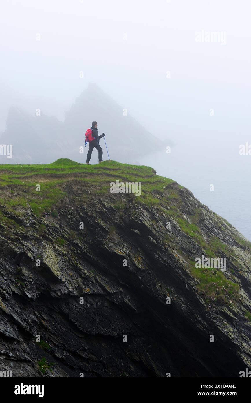United Kingdom, Scotland, Shetland Islands, Senior woman standing on grassy cliff - Stock Image