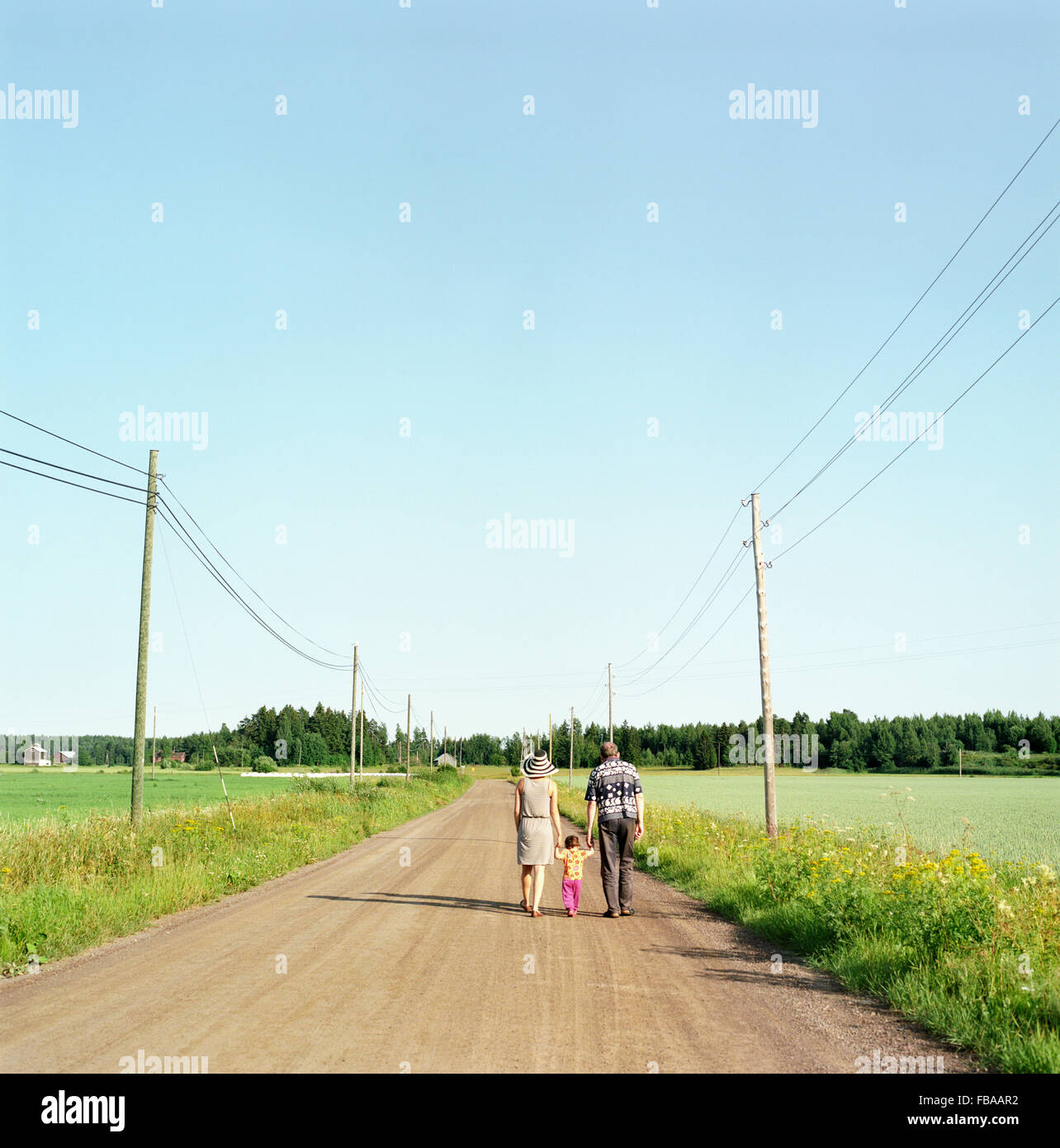 Finland, Uusimaa, Lapinjarvi, Rear view of people with child (2-3) walking along dirt road - Stock Image