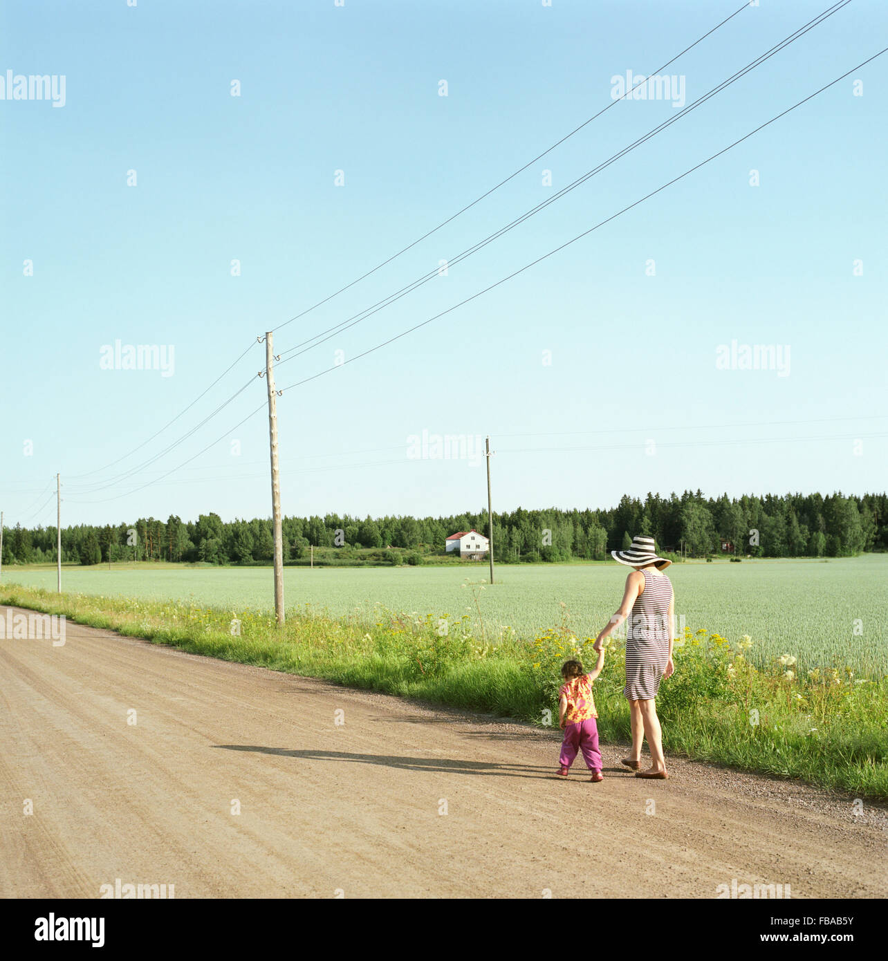 Finland, Uusimaa, Lapinjarvi, Mother and daughter (2-3) walking along dirt road - Stock Image