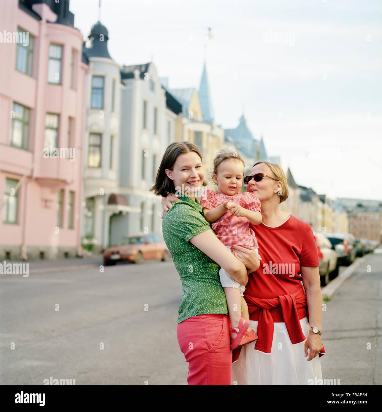 Finland, Uusimaa, Helsinki, Portrait of mother, grandmother and child (2-3) on street - Stock Image